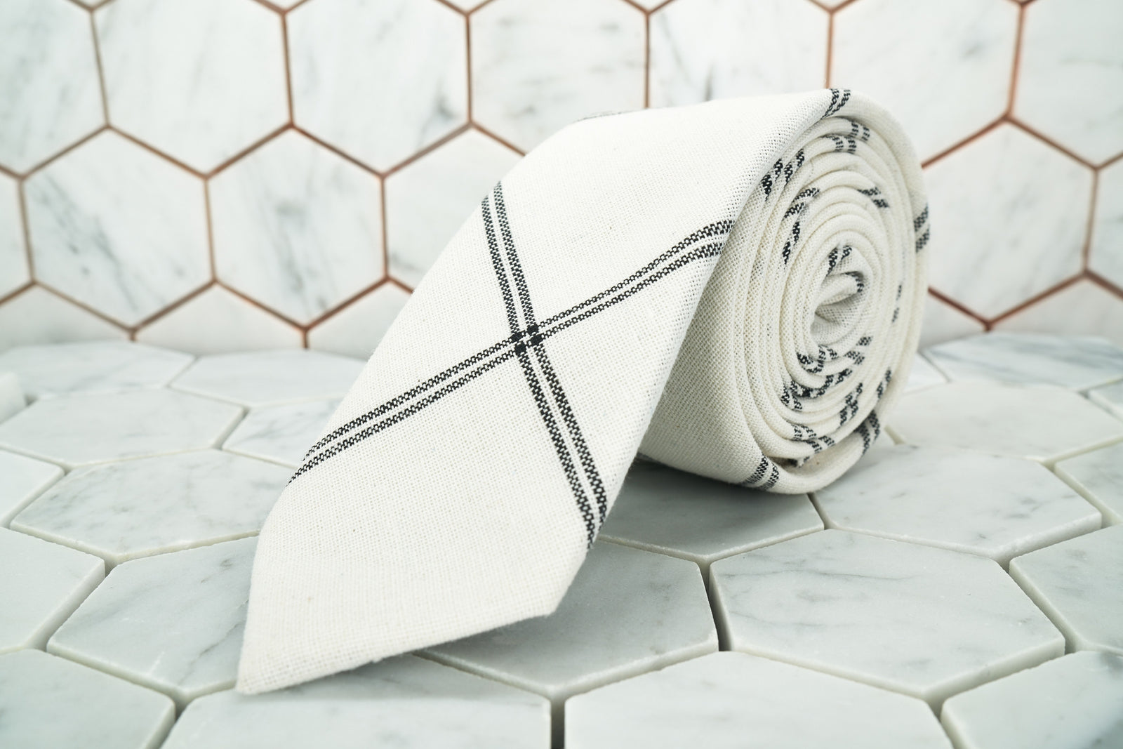 The Ghost White argyle linen necktie made by Dear Martian is rolled up  and lying on a hexagon tiled background.