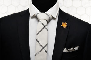 The Lexington Ave necktie is knotted in a half windsor and paired with a rose gold lapel pin and matching white linen pocketsquare made by Dear Martian.