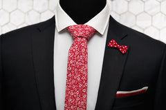 An outfit image featuring a black blazer and white button down shirt. The lapel pin is a bow shaped red polka dot pin and is paired with a red silk knitted pocket square, and the red Shakespeare floral skinny red tie.