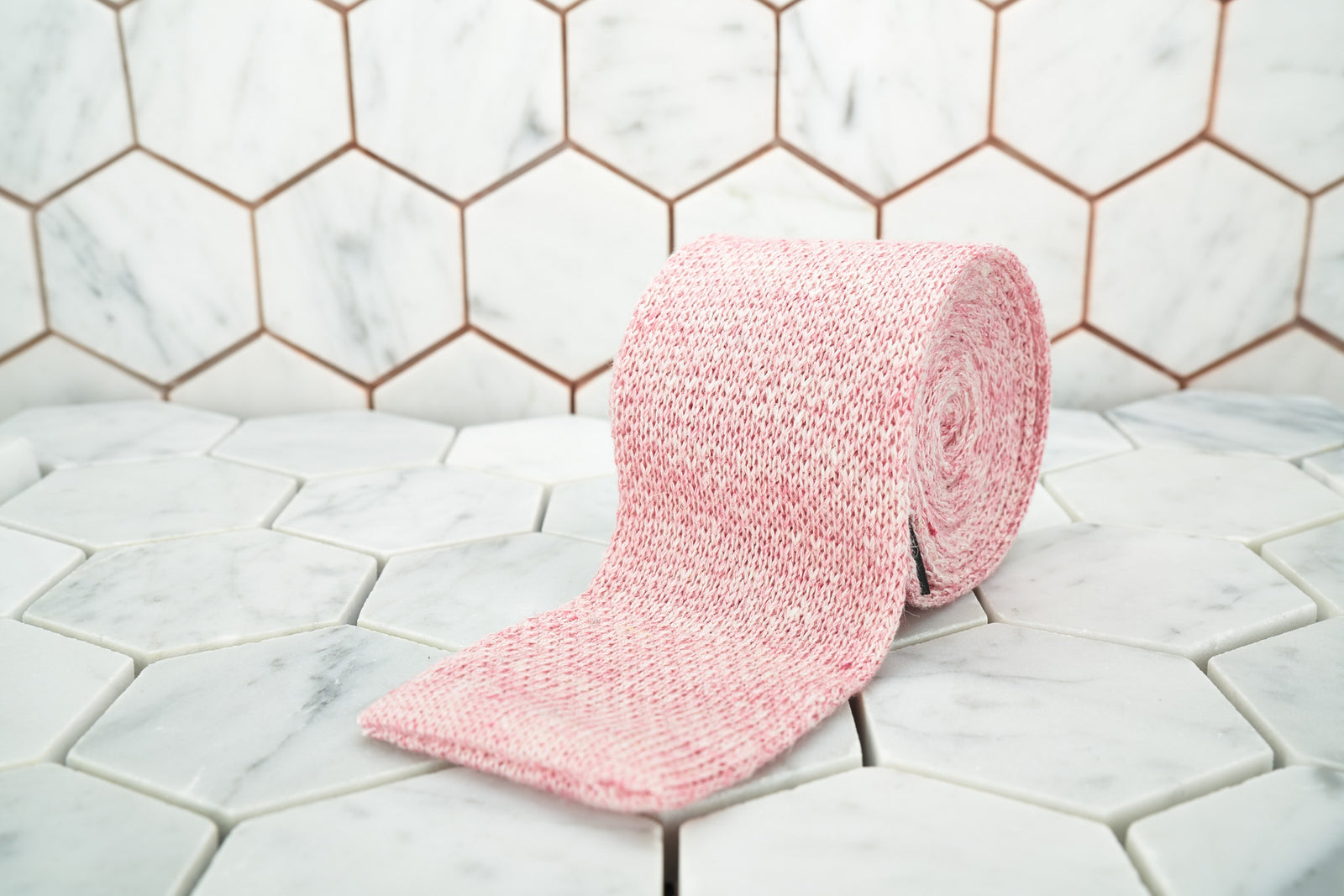 Dear Martian exclusive pink linen knitted tie rolled against a hexagonal background.