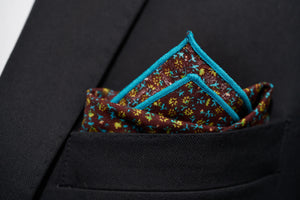 An image of the Ditsy floral pocket square by Dear Martian is show folded in a suit pocket.