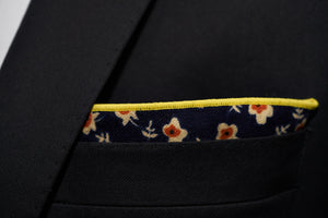 An image of a men's floral pocket square by Dear Martian, is shown folded inside a black suit jacket pocket.