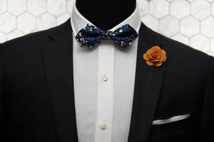 An image of a mannequin styled in Dear Martian products like the diamond pointed Crooke bow tie, white linen handkerchief, and orange flower lapel pin.