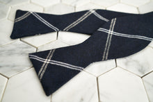 An aerial image of a navy argyle linen blended bow tie by Dear Martian, Brooklyn.
