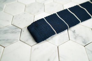 A detailed photo of Dear Martian's Roebling dark blue tie, which is white striped.