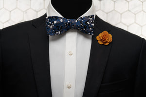 A mannequin rocking an edgy look with the Spotted Steel Blue cotton bow tie and contrasting with a vivid orange lapel pin.