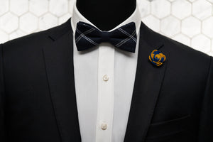 A mannequin wearing the epitome of modern men's fashion; a navy striped bow tie and a yellow and navy flower lapel pin.