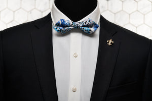 An image of a mannequin modelling a blue diamond pointed bow tie with a golden fleur de lis lapel pin.