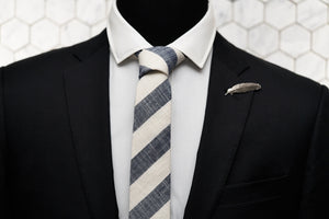 The grey linen blended Dear Martian tie is paired with our exclusive Veder antique silver feather lapel pin is displayed on a mannequin.