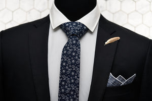 A mannequin is wearing Dear Martian's men accessories, which features our navy paisley tie, the Pratt navy pocket square, and Veder gold feather lapel pin.