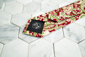 The back of the vibrant Connors paisley red neck tie from Dear Martian, features a DM stitched on the tie's tipping.
