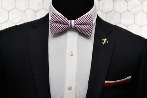 An image of the epitome of men's fashion; a black suit worn by a mannequin with a fleur de list tie clip, red knit pocket square, and patriotic red-white-blue bow tie.