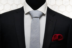 Dear Martian tie with stripes is paired with our men's red knitted pocket square and displayed on a black suit jacket.