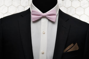 An image of a fitted men's suit with our exclusive pink bow tie and matching brown pocket square.