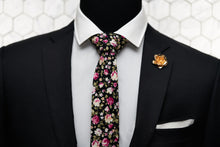 The black floral tie is paired with a rose gold rose lapel pin and a white pocket square. Displayed on a suited mannequin.