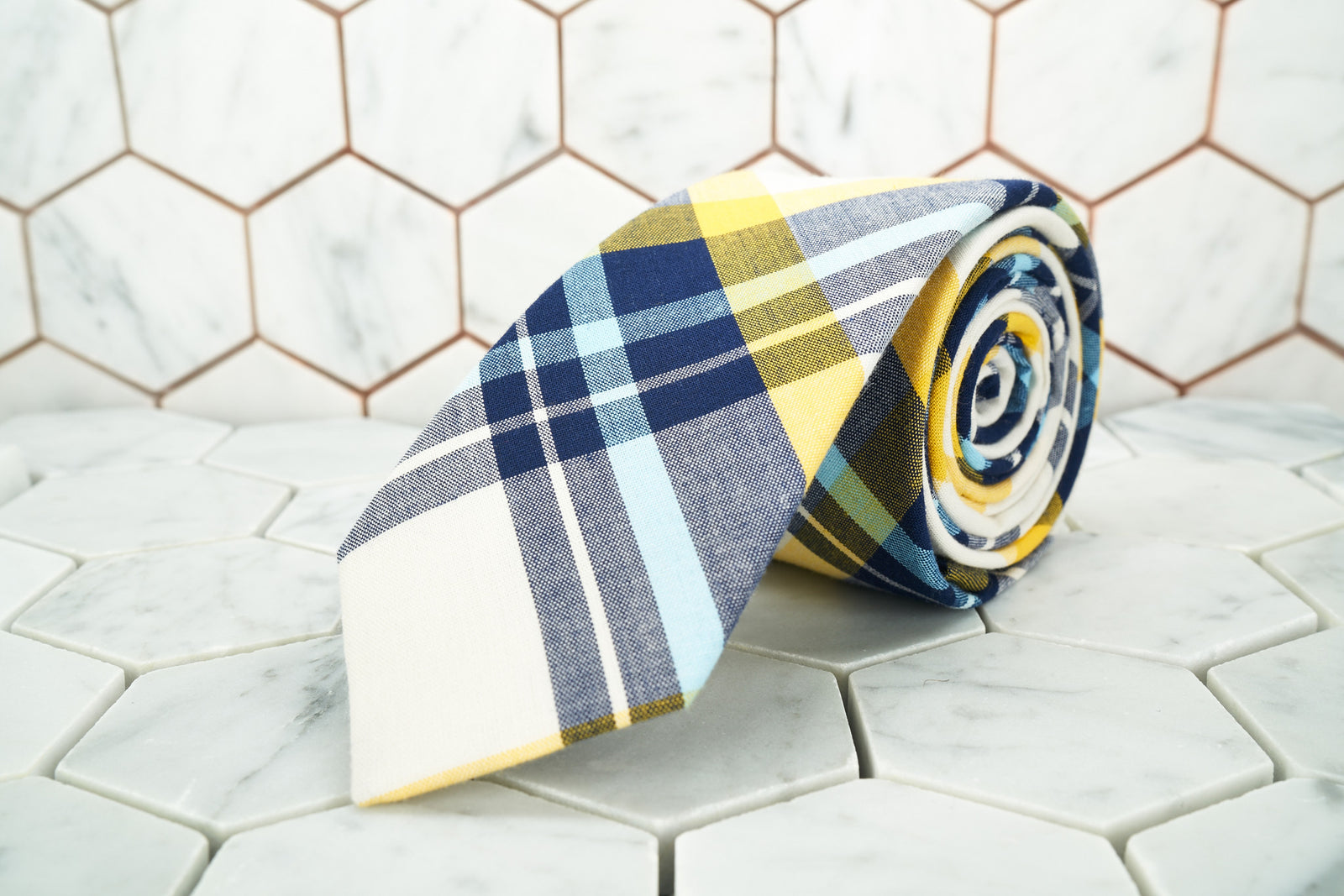 A men's cotton plaid tie from Dear Martian, Brooklyn is rolled up.