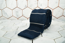 A product image of the Dear Martian midnight navy silk knitted necktie featuring white stripes; the tie is rolled against hexagon tile background.
