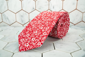 A Dear Martian exclusive floral necktie, featuring an array of white flowers on a vivid red canvas.
