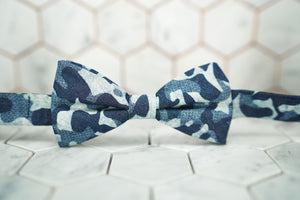 Laying against a white hexagon tiled background, is the Dear Martian, Shipyard denim bow tie that has many blue hues and tones.