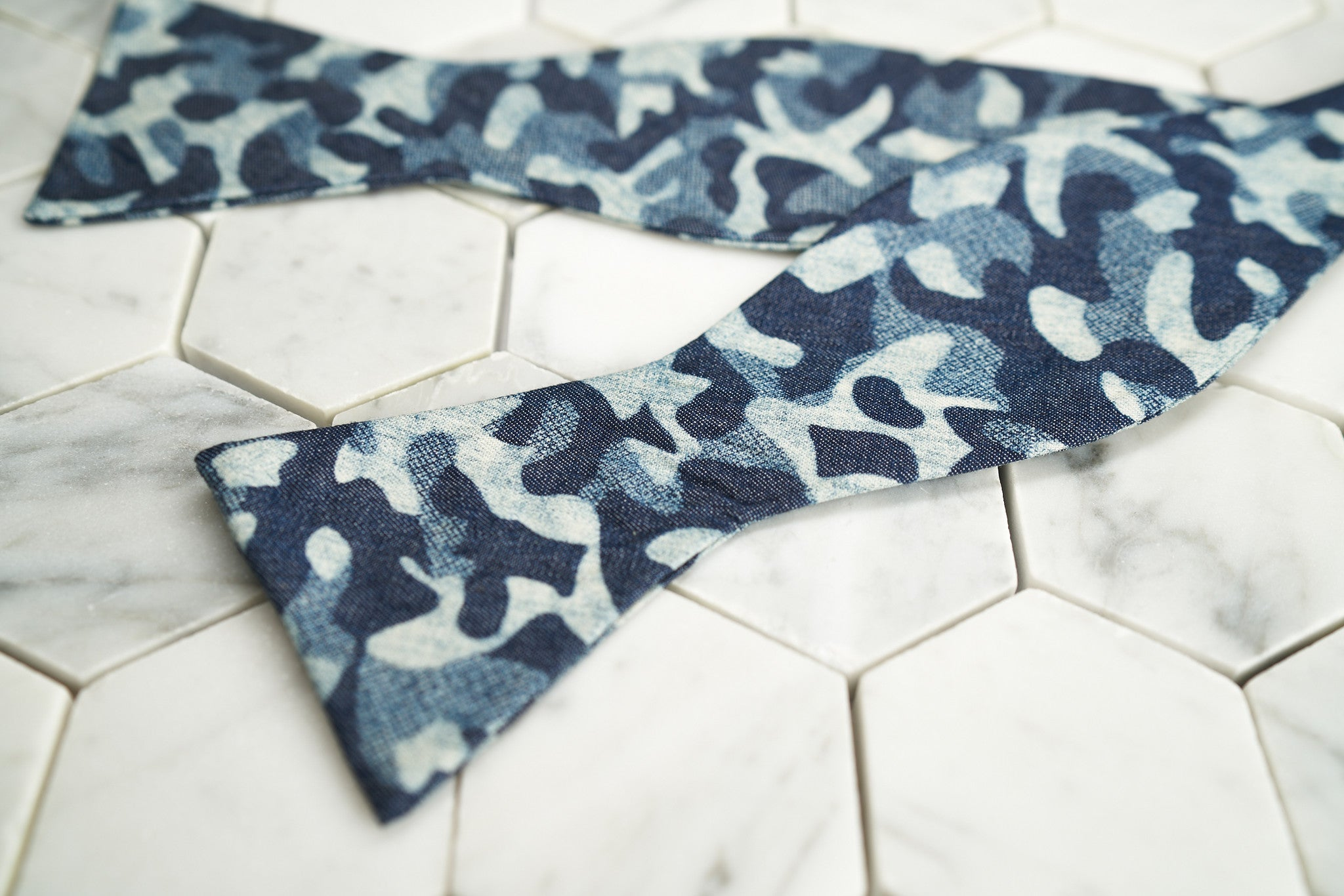 An image of an untied a blue indigo camouflage bow tie, laying across a white hex tile background.
