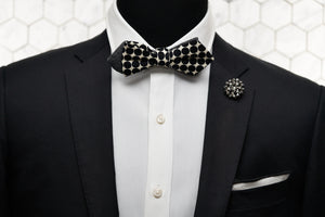 A mannequin dressed in a black and white polka dot bow tie with our DM rhinestone lapel pin and matching pocket square.