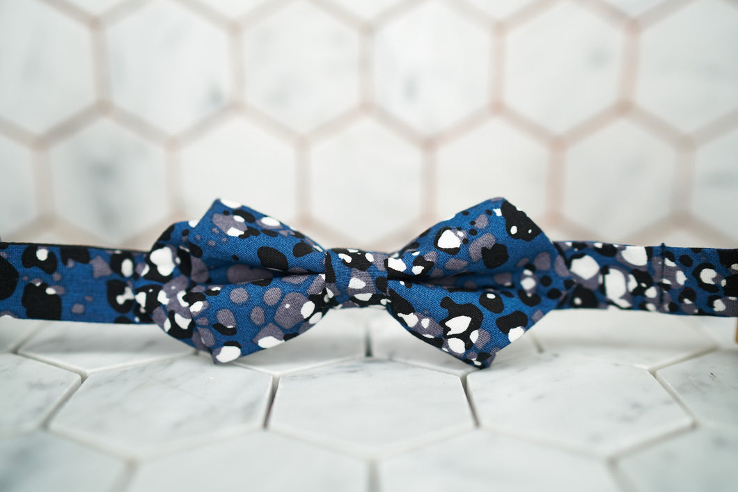 The front of the navy DM jaguar printed diamond pointed bow tie.