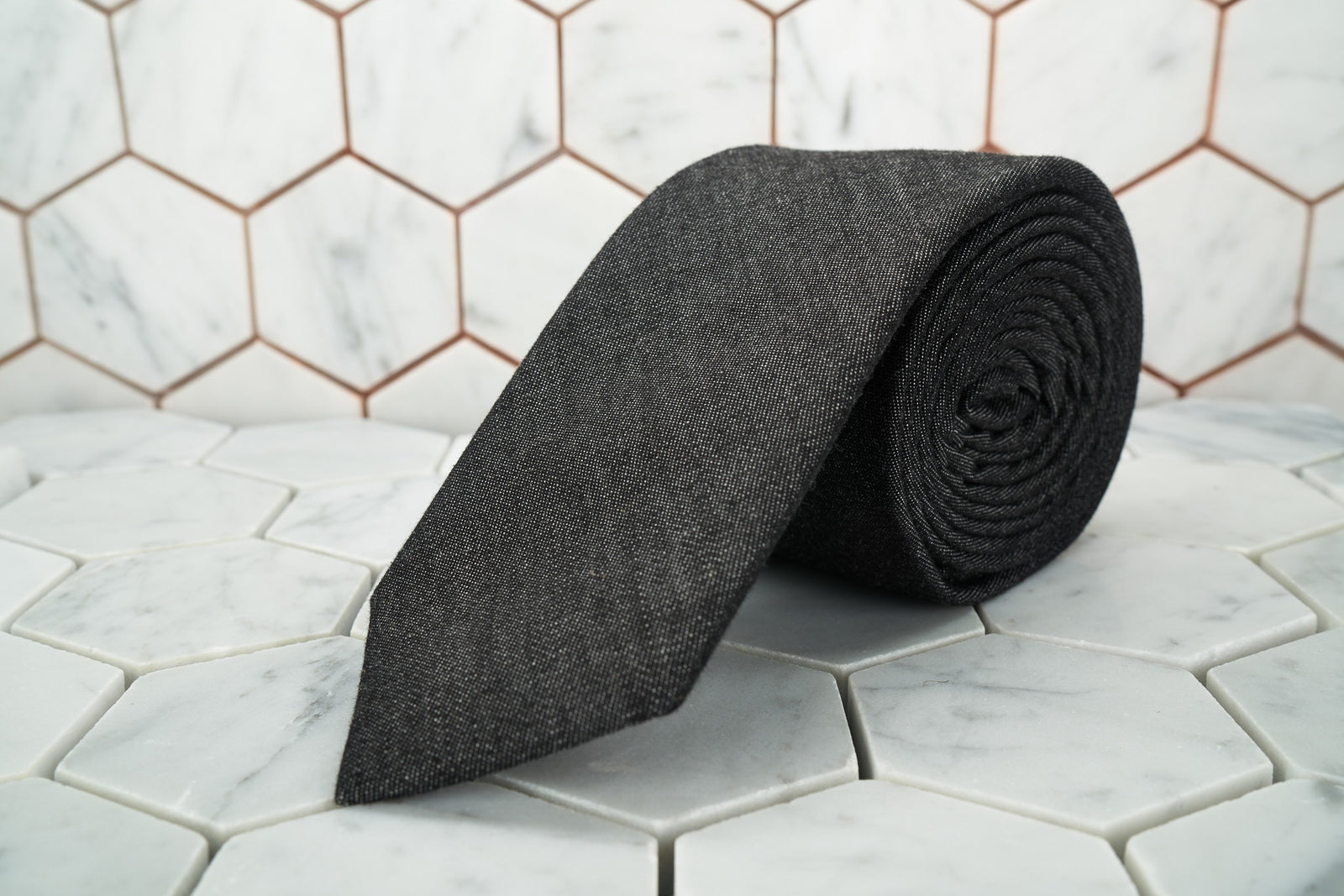 A black denim necktie made by Dear Martian, Brooklyn is shown rolled up and displayed against a hexagonal background.
