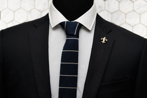 A Dear Martian, navy striped tie modeled on a mannequin wearing a suit. The tie is paired with our Carroll gold fleur de lis lapel pin.