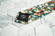 An image that portrays the DM signature hexagonal logo on the back of the Posie floral necktie made by Dear Martian, Brooklyn.