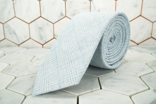 A product image of the Tiffany blue glen-plaid linen necktie rolled up; the tie is exclusively made by Dear Martian.
