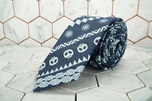 A product image of Dear Martian's Wallabout blue denim skull patterened necktie is rolled up against a white hexagonal background.