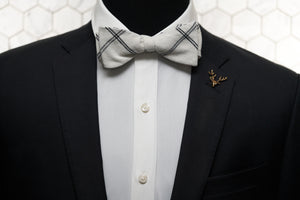 An image of a mannequin wearing both a white checked linen bow tie and gold stag lapel pin.