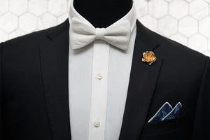 The crepe linen white bow tie is displayed on a mannequin paired with a denim pocket square and rose lapel pin.