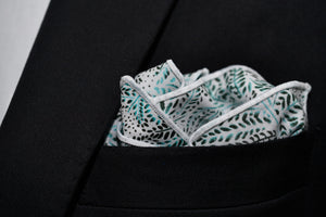An image of Dear Martian, Brooklyn's Whitman cotton white pocket square featuring an array of leaves is shown folded in a pocket.