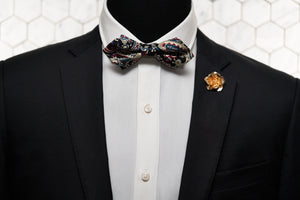 An image of a mannequin wearing the Enchanted, handmade rose gold flower lapel pin and paisley novelty bowtie.