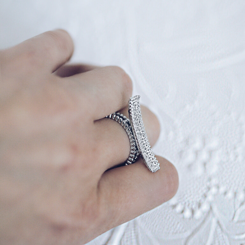 woman wearing Aurum Mod white gold-plated curved bar studded ring