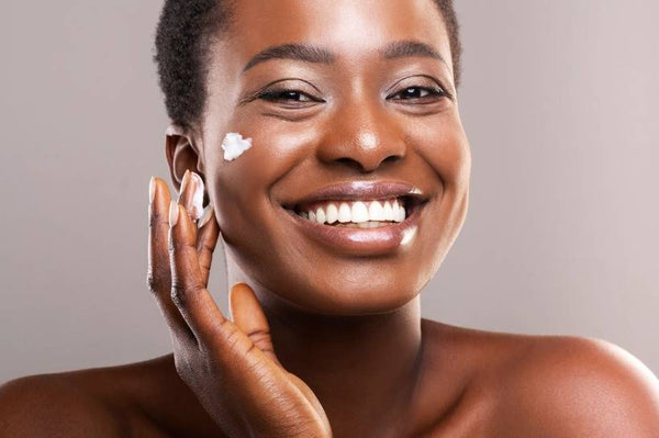 Woman of color applying moisturizer onto her cheek.