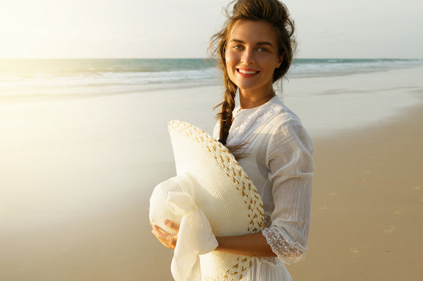 Portrait of beautiful woman with broad-brimmed hat on the beach