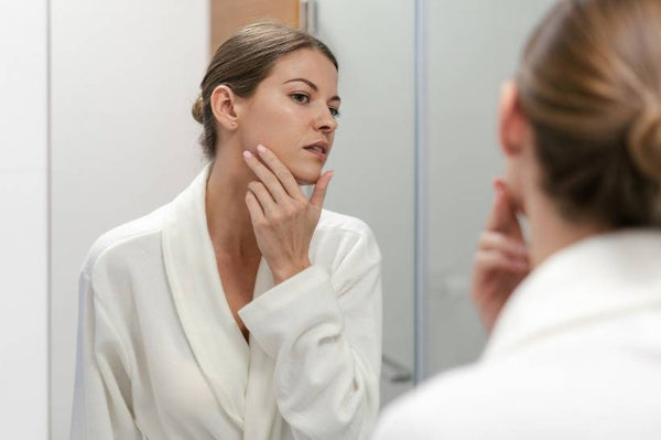 Woman looking into mirror and touching her face