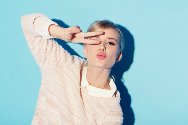 Blonde woman blowing kiss and making peace and love gesture on blue background