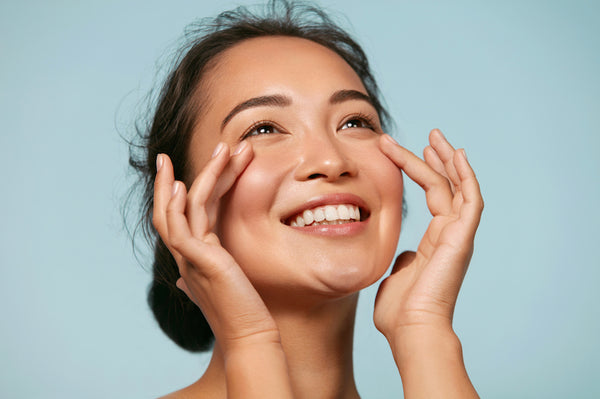 Beautiful smiling asian girl model with natural makeup touching glowing hydrated skin on blue background closeup