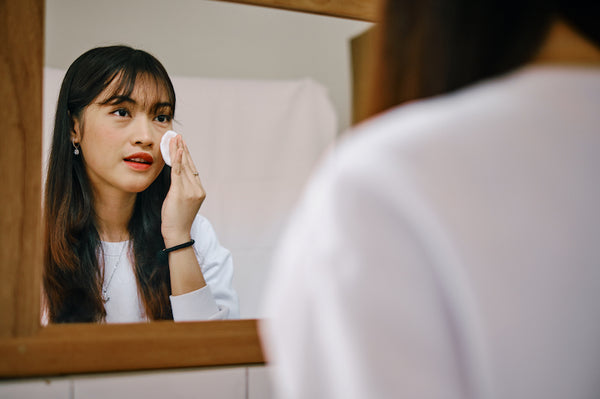 Beautiful Asian woman applying toner with cotton pad in front of mirror