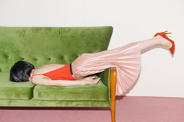 Woman dressed fancy looking defeated facing down on a sofa.