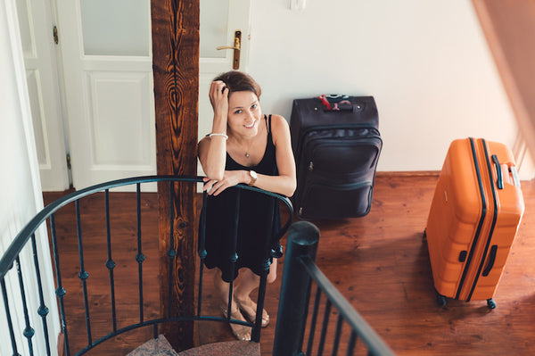 Girl leaning on stairs with two luggages ready for a trip