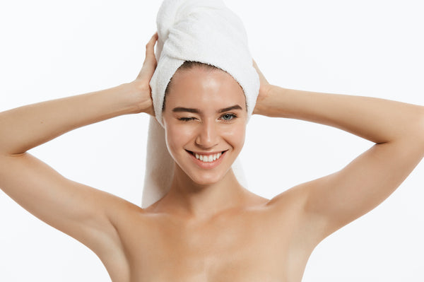 Woman winking and towel drying her hair
