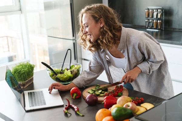 Woman chopping vegetables and looking at her laptop