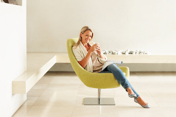 Happy relaxed female drinking coffee in an empty modern room