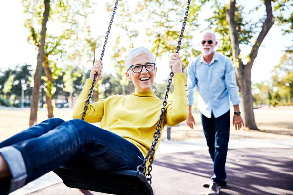 A man is pushing his wife on a swing and she's smiling