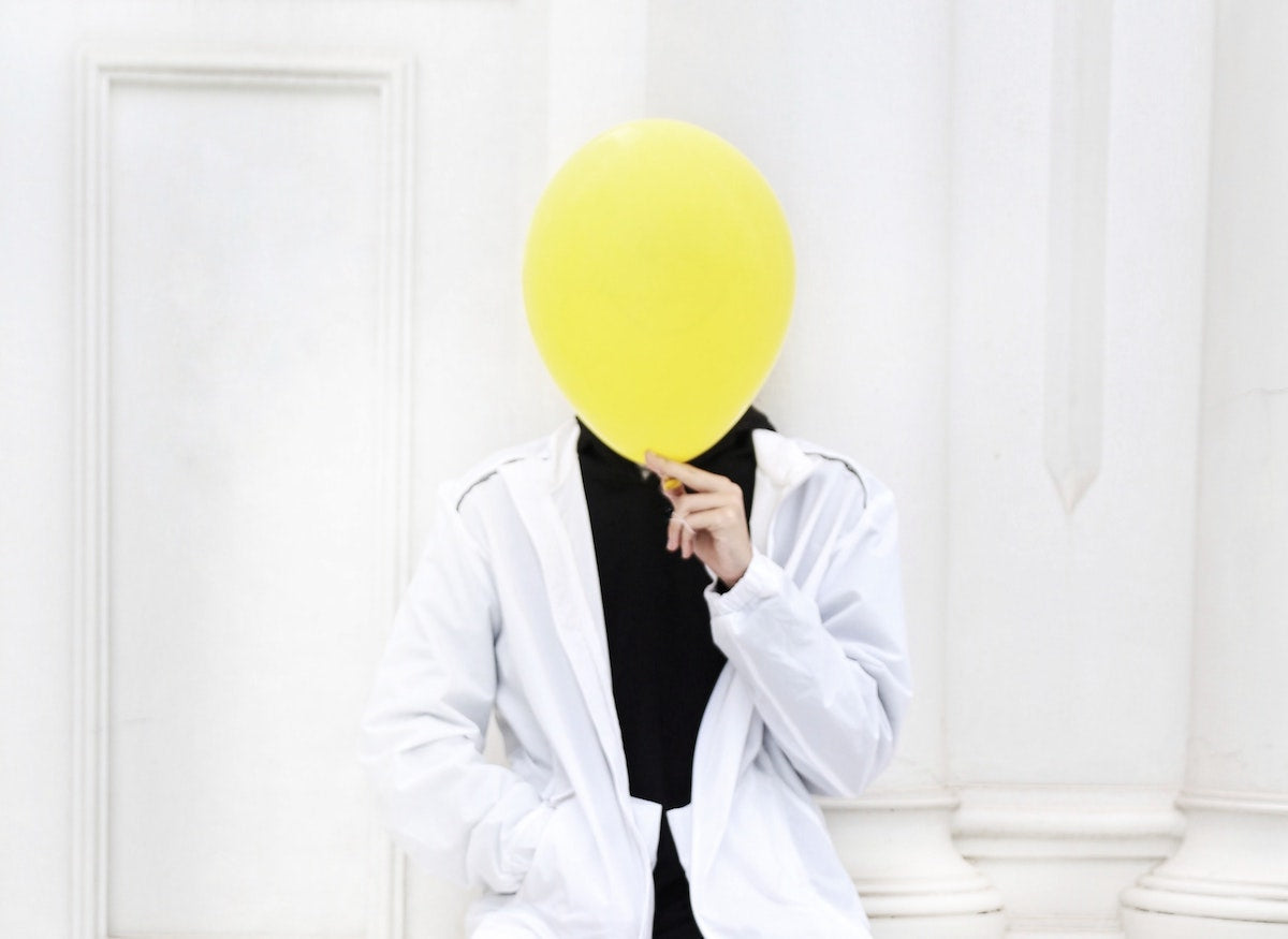 Man with a white jacket sitting with one hand inside a pocket while the other one holds a yellow ballon that covers his face.