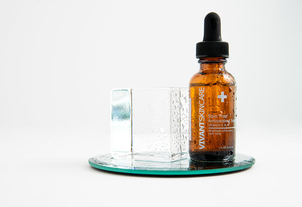 Vivant's Spin Trap Antioxidant Serum with water droplets on the bottle and a cube of ice next to it.